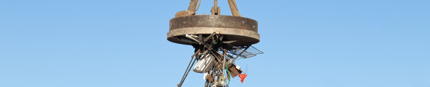 Close up of Large Lifting Electro-Magnet Carrying Scrap Metal